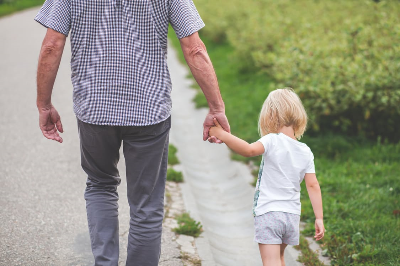 Image of man and child walking on road holding hands