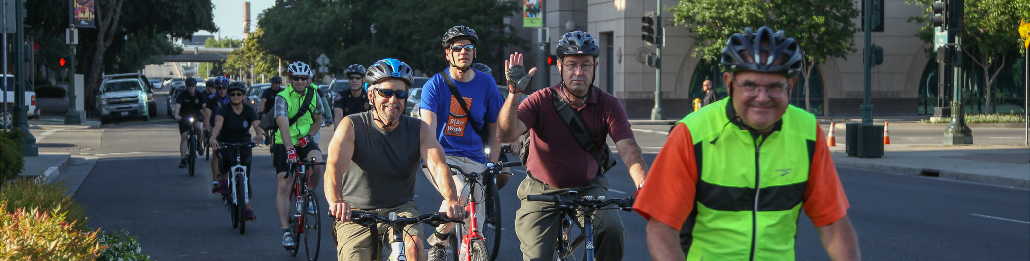 A group of bicyclists wave and smile as they ride during a bike to work event
