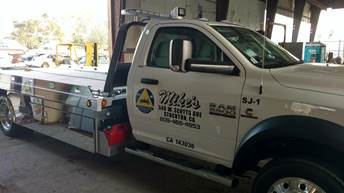 white tow truck from Mike&#39s Towing Company