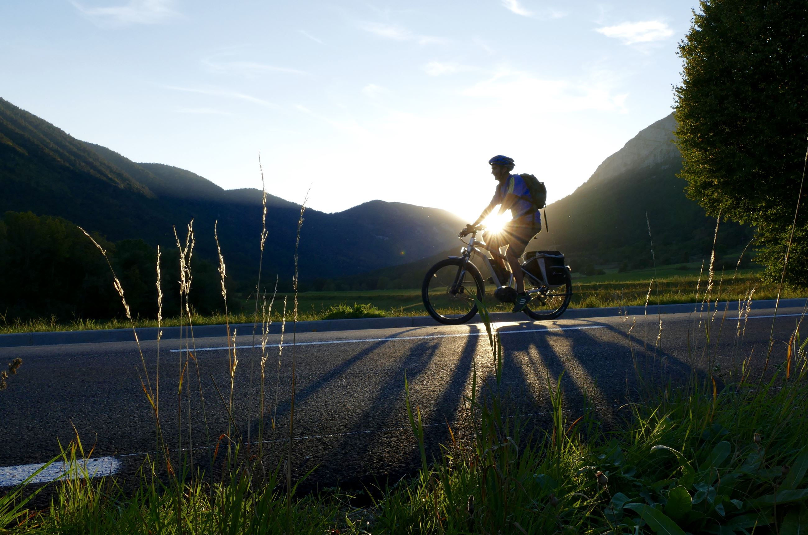 Image of a silhouette of a bicyclist  riding down a road against a sunset and a mountain