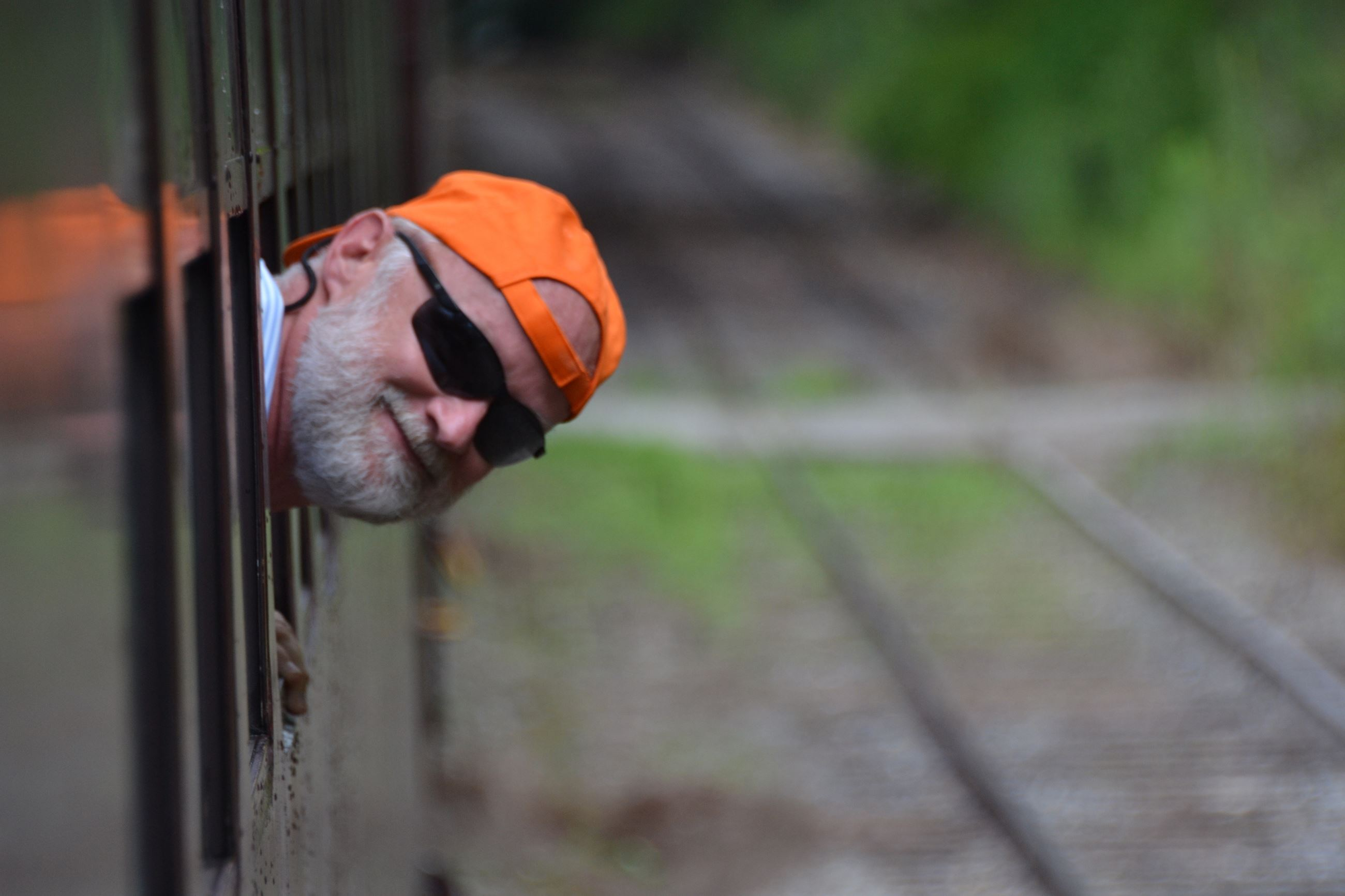 Image of a smiling man in an orange cap peaking his head out of a train window
