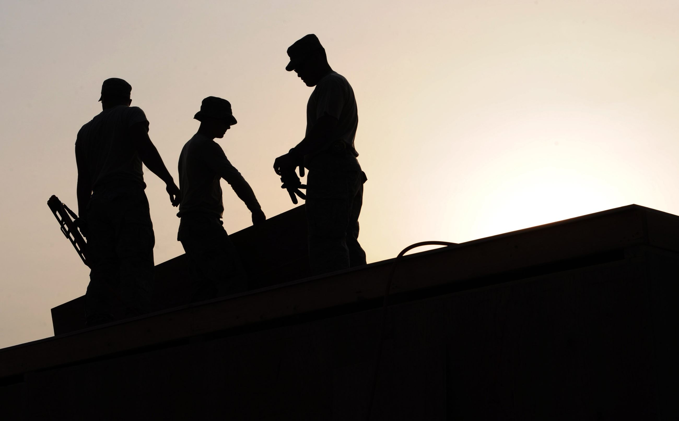 Image of a Sunrise Silhouette of three construction workers with tools