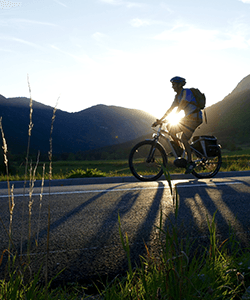 Image of Man on Bike riding down a country road